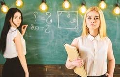 Studenten en stagiairsconcept Het meisje kijkt zeker terwijl de dame die op bordachtergrond schrijven, defocused student stock foto