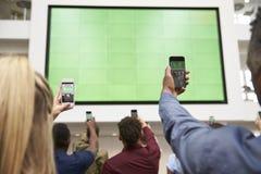 Studenten fotografieren Schirm mit Telefonen, hintere Ansicht, Abschluss oben Lizenzfreie Stockfotos