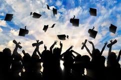 Studenten graduieren die Kappe, die in Himmel wirft lizenzfreies stockbild