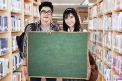 Studenten hält Anschlagtafel in der Bibliothek lizenzfreies stockfoto