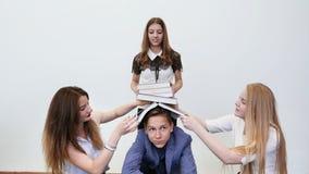 Studenten haben Spaß und spielen mit Büchern Hohe Schüler setzten Bücher auf ihren Freund ` s Kopf lizenzfreies stockbild