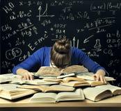 Studenten Hard Study, den trötta uttråkade kvinnan läste böcker över svart tavla Arkivbild