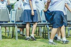 Studenten helfen, den Stuhl zur Mitte des Feldes anzuheben stockfotos