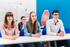Studenten in het drijven van lessen die aandachtig luisteren stock afbeeldingen