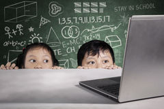 Studenten het gluren laptop met gekrabbel op bord royalty-vrije stock fotografie