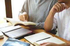 Studenten hilft dem Freund, der abhängiges zusätzliches in der Bibliothek unterrichtet und lernt getrennte alte Bücher lizenzfreies stockfoto