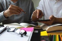 Studenten hilft dem Freund, der abhängiges zusätzliches i unterrichtet und lernt lizenzfreie stockfotos