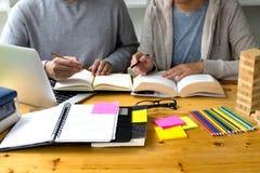 Studenten hilft dem Freund, der abhängiges zusätzliches i unterrichtet und lernt stockfotos