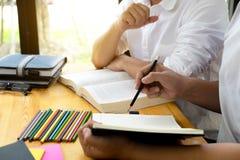 Studenten hilft dem Freund, der abh?ngiges zus?tzliches in der Bibliothek unterrichtet und lernt getrennte alte B?cher lizenzfreies stockbild