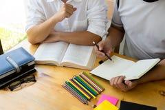Studenten hilft dem Freund, der abh?ngiges zus?tzliches in der Bibliothek unterrichtet und lernt getrennte alte B?cher lizenzfreie stockfotos