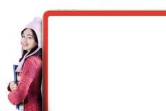 Studenten i vinterkläder lutar på affischtavlan Royaltyfri Bild