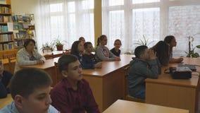 Studenten an ihren Schreibtischen im Klassenzimmer stock video footage
