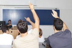 Studenten im Auditorium mit den Händen oben Lizenzfreie Stockfotos