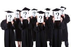 Studenten im Aufbaustudium, die Fragenzeichen zeigen Stockbilder