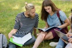 Studenten Junge und Mädchen, die auf dem Grasstudieren sitzen Lizenzfreie Stockfotos