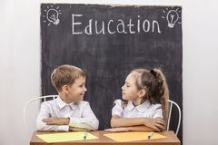 Studenten Junge und Mädchen am Schreibtisch auf dem Hintergrund des Schiefers Lizenzfreie Stockfotos