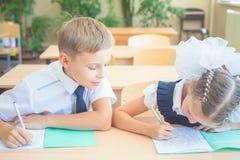 Studenten of klasgenoten in de zitting van het schoolklaslokaal samen bij bureau stock afbeeldingen