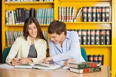 Studenten-Lesebuch zusammen bei Tisch in der Bibliothek Stockbilder