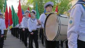 Studenten Marine Academy-Marsches auf einer Parade mit mehrfarbigen Flaggen in ihren Händen, ein junger Seemann mit Stocknahaufna stock video footage