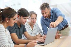 Studenten met leraar die aan laptop werken stock foto's