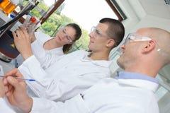 Studenten met leraar tijdens chemieklasse bij universiteit stock foto