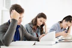 Studenten met notitieboekjes en tabletpc op school Stock Afbeelding