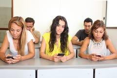 Studenten met slimme telefoons Stock Foto's