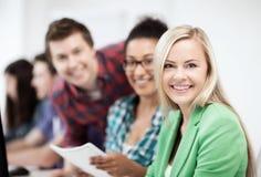 Studenten mit Computer in der Schule studierend Stockbild