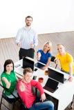 Studenten mit dem Lehrer, der unter Verwendung der modernen Technologien mit den Daumen oben studiert Lizenzfreie Stockfotografie