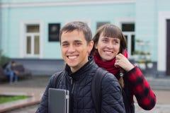 Studenten mit dem Rucksack- und Notizbuchgehen stockbild