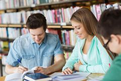 Studenten mit den Büchern, die zur Prüfung in der Bibliothek sich vorbereiten Stockfotografie