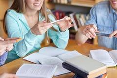 Studenten mit den Smartphones, die Spickzettel machen lizenzfreie stockfotos