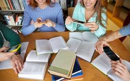 Studenten mit den Smartphones, die Spickzettel machen Lizenzfreies Stockbild