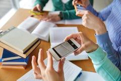 Studenten mit den Smartphones, die Spickzettel machen Lizenzfreie Stockfotografie