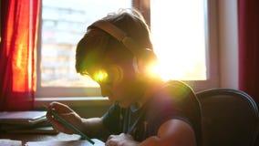 Studenten sitter på ett skrivbord och gör dess jobb Skolutbildning Sol`en s rays till och med exponeringsglaset lager videofilmer