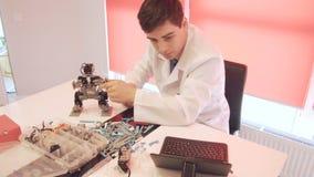 Studenten skapar en robot i laboratoriumet stock video