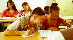 Studenten skriver av från anteckningsbokafrikansk amerikanstudenter royaltyfria bilder