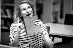 Studenten som läser en bok, har en idé royaltyfria foton