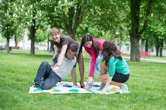 Studenten spielen den Spiel Twister Lizenzfreie Stockfotografie
