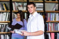 Studenten stehen in einer Bibliothek in Verbindung junger Mann und Frau, die in der Bibliothek spricht stockfoto