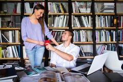 Studenten stehen in einer Bibliothek in Verbindung junger Mann und Frau, die in der Bibliothek spricht stockfotografie