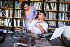 Studenten stehen in einer Bibliothek in Verbindung junger Mann und Frau, die in der Bibliothek spricht stockfotos