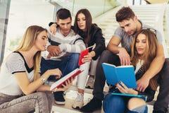Studenten studieren in der Bibliothek Junge Leute verbringen Zeit zusammen Lesebuch und in Verbindung stehende Weile stockfotografie