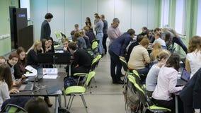 Studenten teilten sich in einige Gruppen, die an den langen Tischen sitzen und die Aufgaben unter Steuerung ihrer Lehrer durchfüh stock video