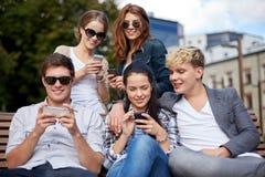 Studenten of tieners met smartphones bij campus stock afbeeldingen