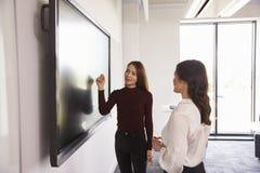 Studenten-And Tutor Discuss-Projekt auf wechselwirkendem Whiteboard lizenzfreie stockfotografie