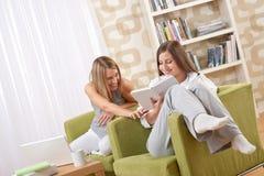 Studenten - Twee vrouwelijke studenten die in zitkamer bestuderen royalty-vrije stock foto's