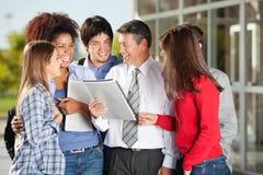 Studenten und Lehrer With Book Standing an Stockfoto