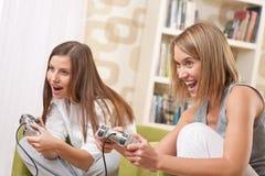 Studenten - vrouwelijke tiener Twee die het spel van TV speelt Stock Afbeelding