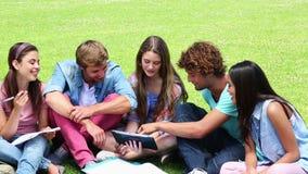 Studenten, welche die Außenseite zusammen spricht sitzen stock video footage